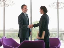 Businessman shaking hands with businesswoman in modern office cafeteria
